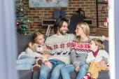 Fényképek boldog család két imádnivaló gyerekek együtt fotelben ülve, karácsonykor