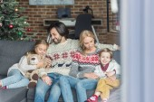 Fényképek boldog család, két gyermek együtt fotelben ülve, karácsonykor