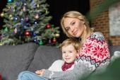 glückliche Mutter und niedlichen kleinen Sohn zusammen auf der Couch sitzen und Lächeln in die Kamera zu Weihnachten