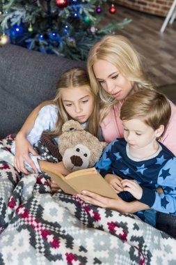 "Картина, постер, плакат, фотообои ""высокий угол зрения молодой матери, чтение книги с мило детей в пижаме на Рождество "", артикул 213565232"