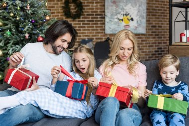 happy family with two adorable kids opening christmas gifts together