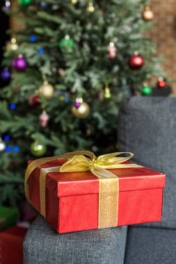 close-up view of red gift box with golden bow on couch and decorated christmas tree behind