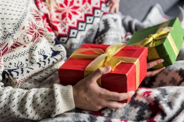 cropped shot of young couple in winter sweaters holding christmas presents
