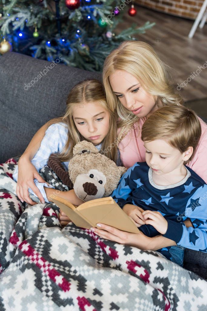 high angle view of young mother reading book with cute children in pajamas at christmas time