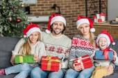 Fényképek boldog család santa kalap tartja karácsonyi ajándékokat, és mosolyogva kamera