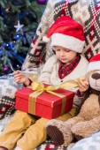 Fotografie entzückende kleine Junge in Nikolausmütze öffnen Weihnachtsgeschenk