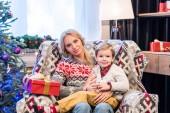 krásná šťastná matka a syn sedí pohromadě a usmívá se na kamery v době Vánoc
