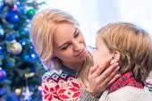 schöne junge Mutter betrachten entzückenden kleinen Sohn in der Weihnachtszeit