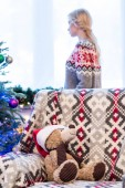 teddy bear in santa hat on couch and young woman standing near christmas tree behind