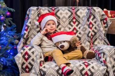 adorable little boy holding teddy bear in santa hat and smiling at camera at christmas time