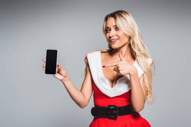attractive woman in christmas dress pointing by finger at smartphone with blank screen isolated on grey background