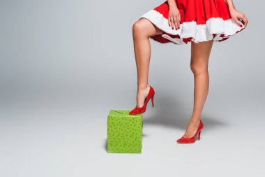 cropped image of sexy young woman in christmas dress standing on gift box by one leg in shoes with heels on grey background