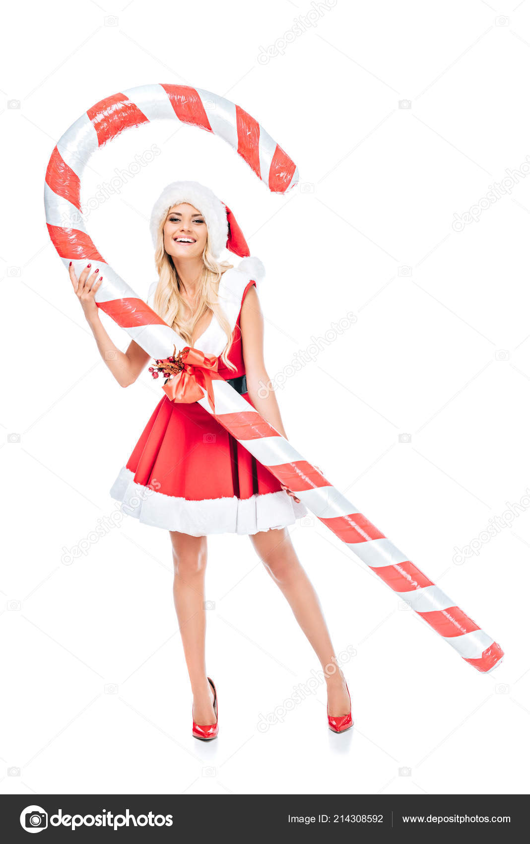 smiling woman santa dress christmas hat standing big striped candy
