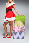 partial view of sexy santa girl in christmas dress holding gift boxes on grey background