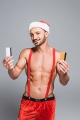 Fotografie handsome muscular man in christmas hat showing credit cards isolated on grey background