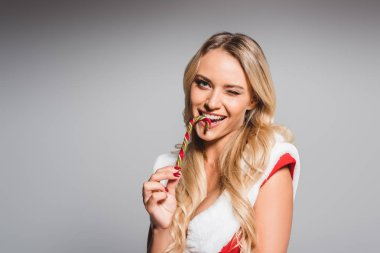 happy young woman in santa dress eating striped christmas stick isolated on grey background
