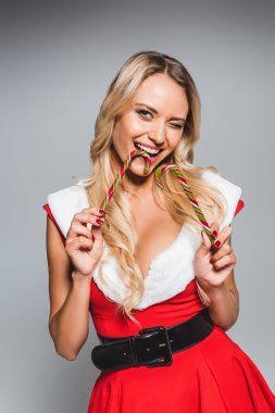 happy young woman in christmas dress holding two striped candy sticks isolated on grey background