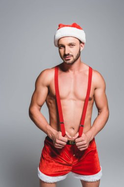 confident sexy man in christmas hat and shorts holding suspenders isolated on grey background
