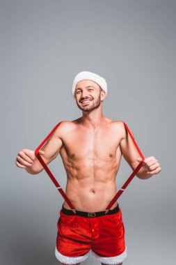 laughing shirtless muscular man in christmas hat and shorts holding suspenders isolated on grey background