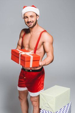 happy muscular santa in christmas hat and shorts holding gift box isolated on grey background