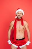 Fotografie lächelnd muskulösen nackter Oberkörper Mann in weihnachtshut und Roter Schal berühren eigenen Shorts auf rotem hintergrund isoliert