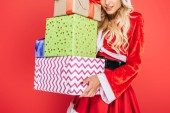 partial view of santa girl in christmas dress holding pile of gift boxes isolated on red background