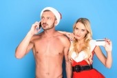 Fotografie Nackter Oberkörper muskulöser Mann in weihnachtsmütze sprechen auf Smartphone während seiner Freundin zeigt Kreditkarte isoliert auf weißem Hintergrund