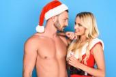 Fotografie Seitenansicht von nacktem Oberkörper muskulöser Mann in Weihnachten Hut umarmende schöne Freundin in Santa Kleid auf blauem Hintergrund isoliert