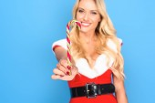 selective focus of happy woman in santa dress holding christmas stick isolated on blue background