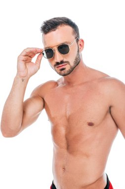 serious muscular shirtless man adjusting sunglasses and looking at camera isolated on white background