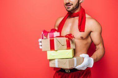 partial view of muscular shirtless sexy man in red scarf holding pile of christmas presents isolated on red background