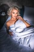 verführerische nackte junge Frau, die im Bett liegt und ihren Körper unter Sonnenuntergang mit einer Decke bedeckt