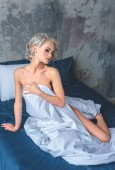 seductive naked young woman sitting on bed and covering her body with blanket