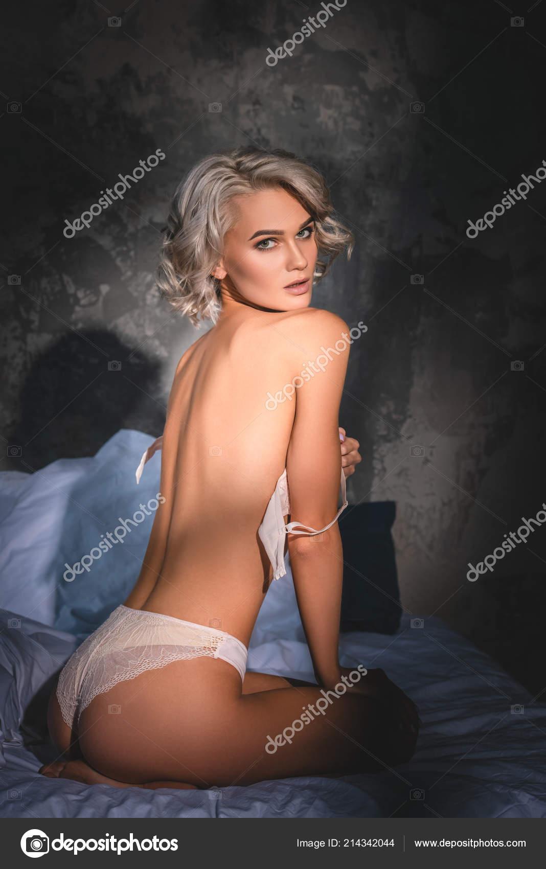 82e36465b4 Sexy mujer joven en ropa interior sentada en la cama quitándose el  sujetador y mirando a cámara bajo los rayos del atardecer — Foto de ...
