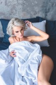 Fotografie high angle view of attractive naked young woman lying in bed under blanket and looking away
