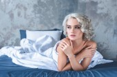 Photo seductive young woman sitting in bed covered with white blanket