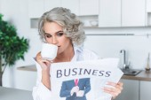 Fotografie beautiful young woman in white shirt reading newspaper with coffee at kitchen in morning