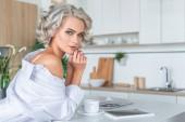 Fotografie atraktivní mladá žena v bílé košili s tabletu a coffee cup v kuchyni ráno
