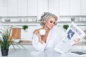 atraktivní mladá žena v bílé košili čtenářský deník s kávou v kuchyni ráno