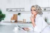 atraktivní mladá žena v bílé košili držení tabletu a koukal na kuchyni ráno