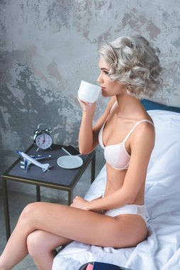 attractive young woman in underwear sitting on bed and drinking coffee