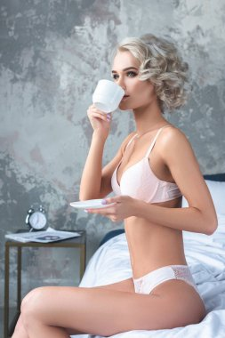 Seductive young woman in underwear sitting on bed and drinking coffee stock vector