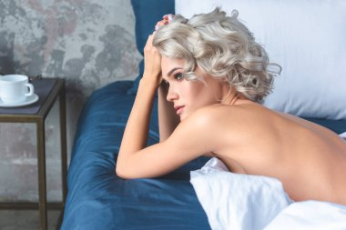attractive naked young woman lying on bed and looking away
