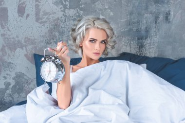 attractive young woman lying in bed and holding vintage alarm clock