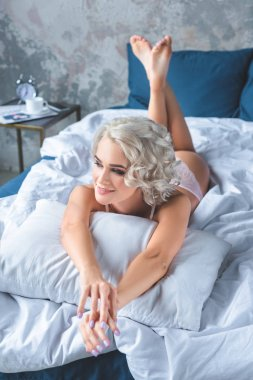 happy young woman lying on bed in underwear