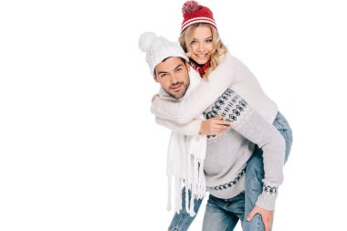 beautiful happy young couple in sweaters, scarves and hats piggybacking and smiling at camera isolated on white