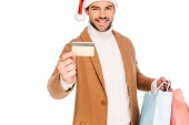 Fotografie happy young man in santa hat holding credit card and shopping bags isolated on white