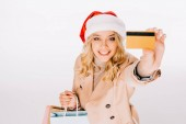 high angle view of beautiful smiling young woman in santa hat holding credit card and shopping bags isolated on white
