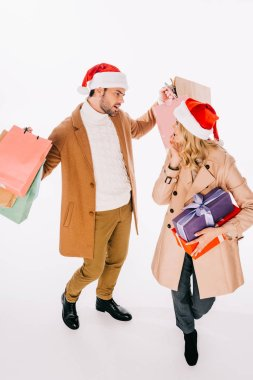 high angle view of young couple in santa hats holding gift boxes and shopping bags isolated on white