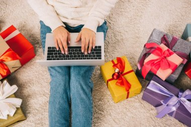 cropped shot of young woman using laptop while sitting near christmas gifts